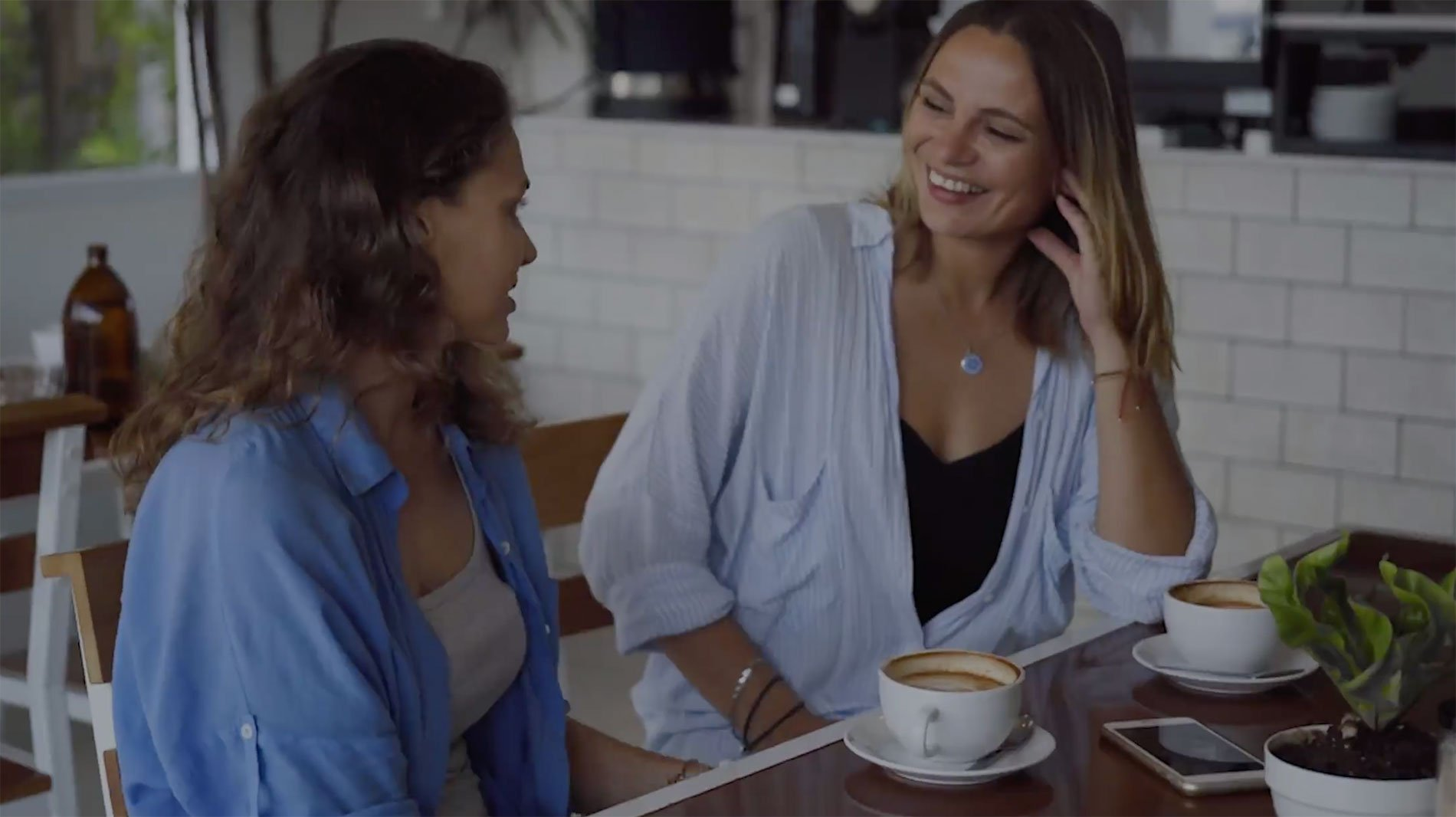 Two friends enjoying coffee as they chat in local cafe - screenshot from feature video