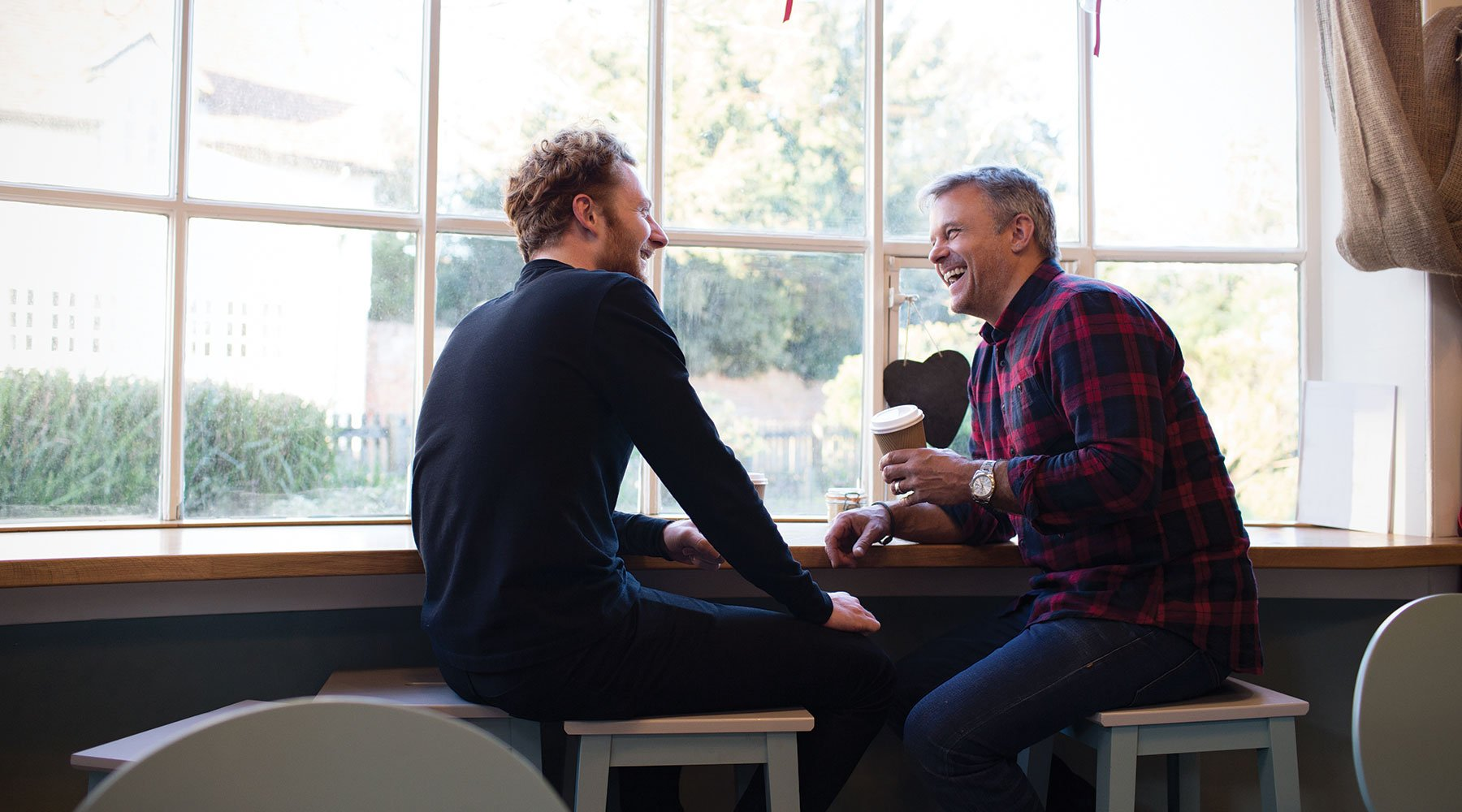 Son and father sitting together laughing in a coffee shop