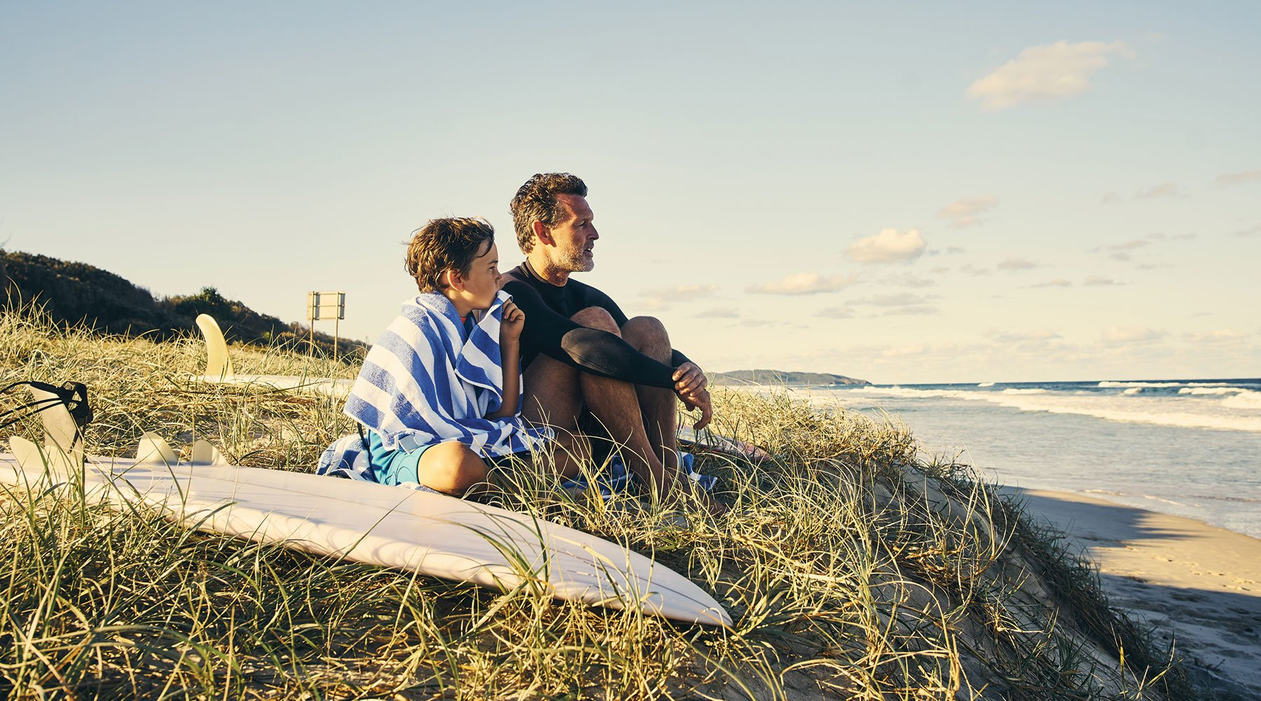A Perth father and son sitting together on beach after surfing