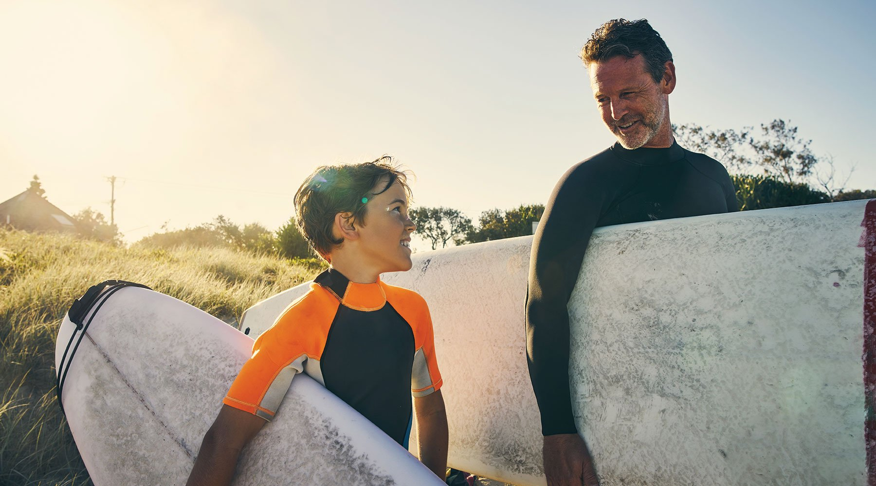 Father and young son about to go surfing together in Perth, Western Australia