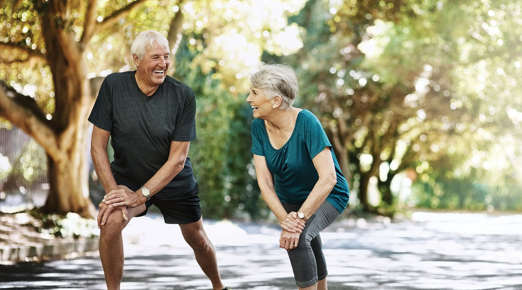 Grandparents stretching in the park to maintain their physical health
