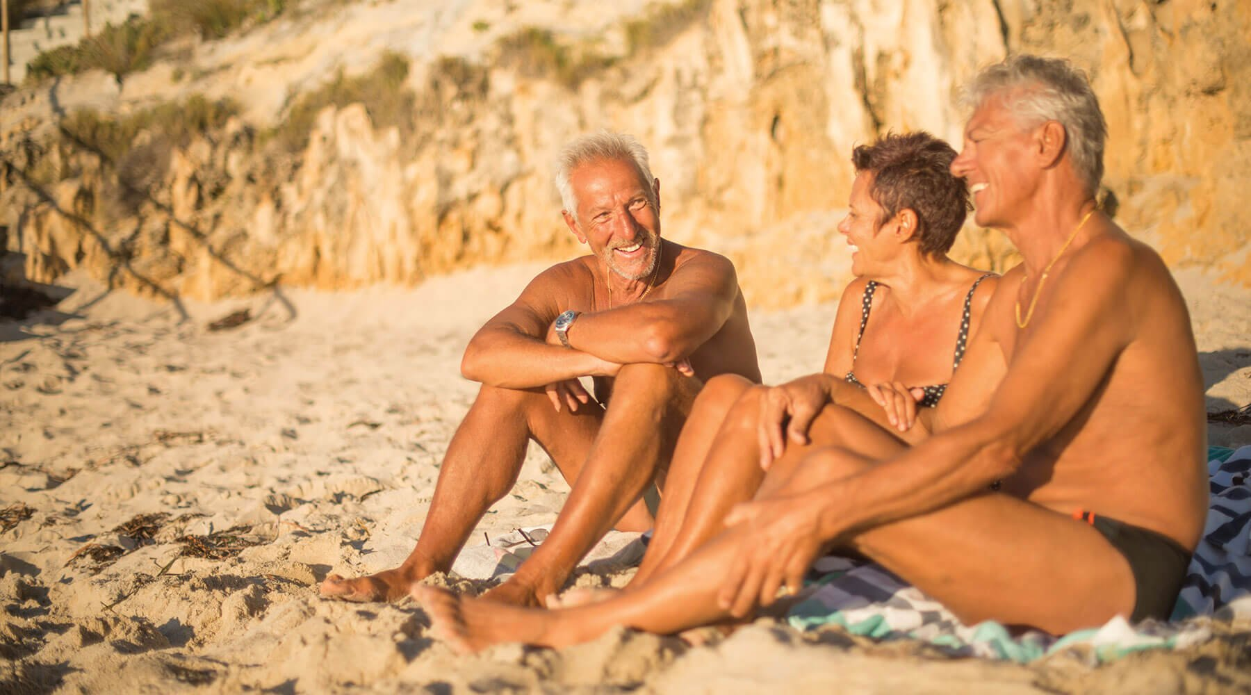Group of 60-year-old's having a laugh on the sand at beach