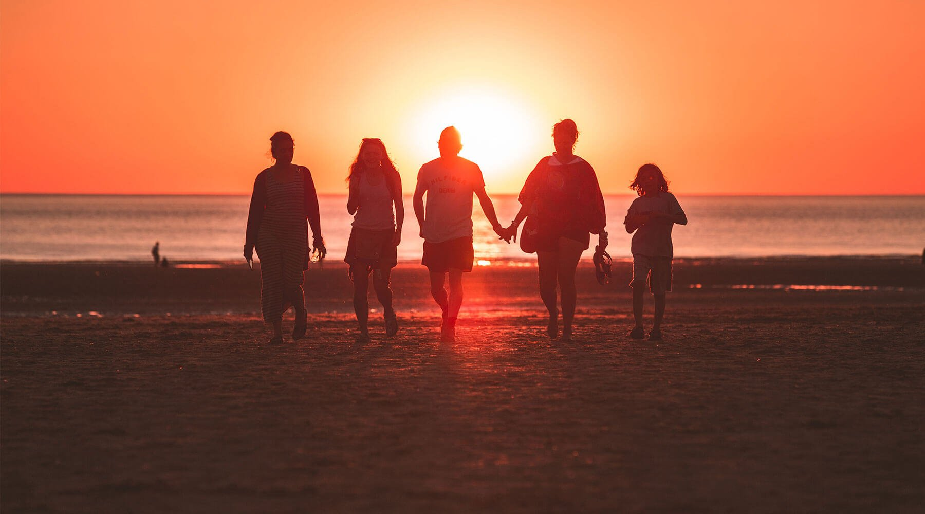 Group of friends walking on beach as sunsets for 360 Health + Community's vision and mission header