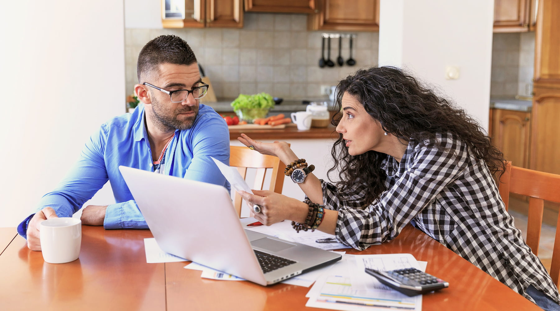 Recovery Coach image of man and women talking over paperwork at kitchen table